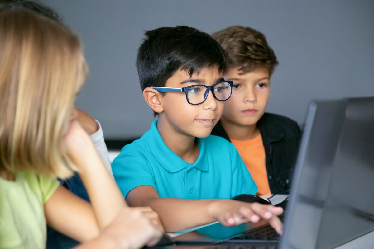 Boy learning with friends on computer